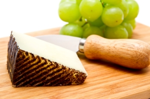 Manchego cheese ang grapes on chopping board