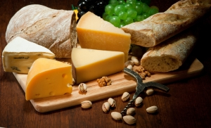 Various types of cheese with bread and fruit